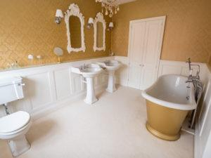 Elegant Panelled Bathroom with Gold Freestanding Bath